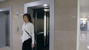 Νέα επιχειρηματίας πιπεροριζών στο κοστούμι που περπατεί από τον ανελκυστήρα απόθεμα βίντεο