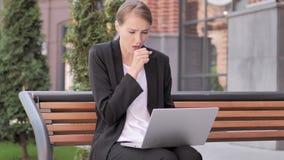 Νέα επιχειρηματίας που βήχει εργαζόμενη στο lap-top υπαίθριο απόθεμα βίντεο