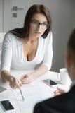 Νέα επιχειρηματίας που δείχνει ένα έγγραφο με μια μάνδρα Στοκ εικόνα με δικαίωμα ελεύθερης χρήσης