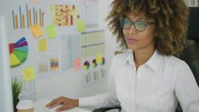 Νέα επιχειρηματίας που εξερευνά τα διαγράμματα στον υπολογιστή φιλμ μικρού μήκους