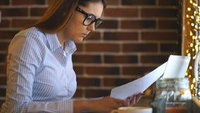 Νέα επιχειρηματίας που εξετάζει το έγγραφο και που δακτυλογραφεί στο lap-top απόθεμα βίντεο