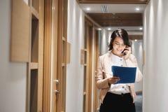 Νέα επιχειρηματίας που εργάζεται στην οικονομική ομιλία αντιπροσωπείας στο τηλέφωνο κυττάρων στοκ εικόνα