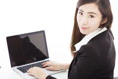 Νέα επιχειρηματίας που κάθεται και που χρησιμοποιεί ένα lap-top Στοκ Φωτογραφίες
