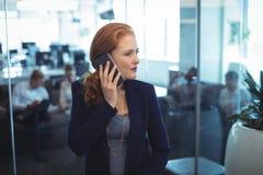 Νέα επιχειρηματίας που κοιτάζει μακριά παίρνοντας το κινητό τηλέφωνο Στοκ Εικόνες