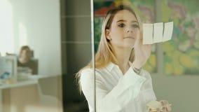 Νέα επιχειρηματίας που κολλά τις κολλώδεις σημειώσεις για το γυαλί στο γραφείο απόθεμα βίντεο