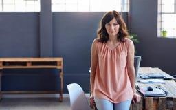 Νέα επιχειρηματίας που κλίνει σε ένα γραφείο σε ένα γραφείο Στοκ Φωτογραφία