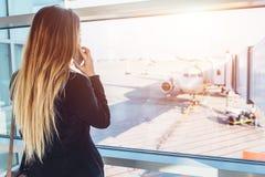 Νέα επιχειρηματίας που μιλά στο κινητό τηλέφωνο που περιμένει την πτήση της που εξετάζει τα αεροπλάνα μέσω του παραθύρου που στέκ Στοκ φωτογραφίες με δικαίωμα ελεύθερης χρήσης