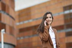 Νέα επιχειρηματίας που μιλά με ένα smartphone στο αστικό backgroun Στοκ Εικόνα
