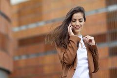 Νέα επιχειρηματίας που μιλά με ένα smartphone στο αστικό backgroun Στοκ Φωτογραφία