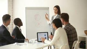 Νέα επιχειρηματίας που παρουσιάζει στην πολυ-εθνική ομάδα, που ρωτά απαντώντας στις ερωτήσεις