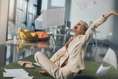 Νέα επιχειρηματίας που ρίχνει τα έγγραφα καθμένος στο πάτωμα στην αρχή Στοκ φωτογραφία με δικαίωμα ελεύθερης χρήσης