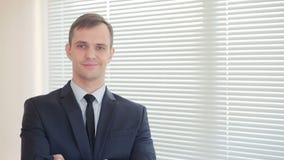 Νέα επιχειρηματίας που στέκεται στην αρχή στο υπόβαθρο των κουρτινών που εξετάζουν τη κάμερα και το χαμόγελο απόθεμα βίντεο