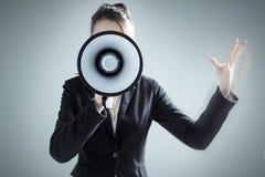 Νέα επιχειρηματίας που φωνάζει πέρα από megaphone Στοκ Φωτογραφία