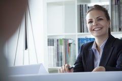 Νέα επιχειρηματίας που χαμογελά στο γραφείο κατά τη διάρκεια μιας επιχειρησιακής συνεδρίασης Στοκ φωτογραφίες με δικαίωμα ελεύθερης χρήσης