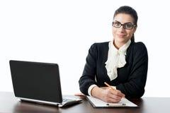 Νέα επιχειρηματίας που χαμογελά στο μπροστινό γραφείο Στοκ Φωτογραφίες