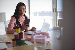 Νέα επιχειρηματίας που χρησιμοποιεί το κινητό τηλέφωνο στο γραφείο γραφείων Στοκ εικόνες με δικαίωμα ελεύθερης χρήσης