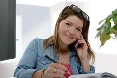 Νέα επιχειρηματίας που χρησιμοποιεί το τηλέφωνό της στο γραφείο της Στοκ φωτογραφία με δικαίωμα ελεύθερης χρήσης