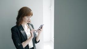 Νέα επιχειρηματίας που χρησιμοποιεί το smartphone που υπερασπίζεται το παράθυρο στο εσωτερικό γραφείων απόθεμα βίντεο