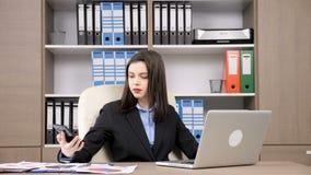 Νέα επιχειρηματίας στη δακτυλογράφηση γραφείων της στο lap-top που απαντά έπειτα στο τηλέφωνο απόθεμα βίντεο