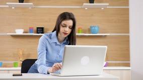 Νέα επιχειρηματίας στη δακτυλογράφηση κουζινών στο lap-top φιλμ μικρού μήκους