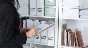 Νέα επιχειρηματίας στο γραφείο που κρατά έναν φάκελλο Στοκ Εικόνα