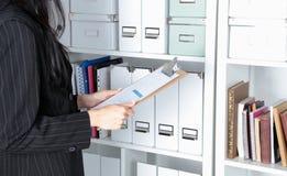 Νέα επιχειρηματίας στο γραφείο που κρατά έναν φάκελλο Στοκ Εικόνες