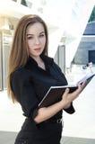 Νέα επιχειρηματίας στο μαύρο φόρεμα με ένα ανοικτό σημειωματάριο Στοκ εικόνες με δικαίωμα ελεύθερης χρήσης