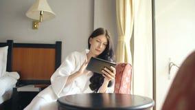 Νέα επιχειρηματίας στο μπουρνούζι που χρησιμοποιεί τη συνεδρίαση υπολογιστών ταμπλετών στην καρέκλα στο δωμάτιο ξενοδοχείου απόθεμα βίντεο