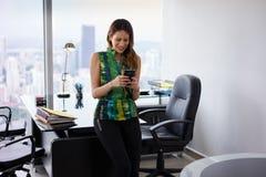 Νέα επιχειρηματίας του Λατίνα με το τηλέφωνο στο σύγχρονο γραφείο Στοκ Εικόνες