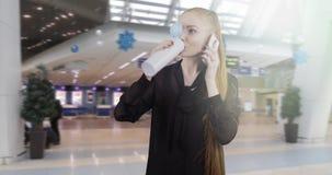Νέα επιχειρησιακή γυναίκα με τις μακροχρόνιες κόκκινες συζητήσεις τρίχας σε ένα κινητό τηλέφωνο απόθεμα βίντεο