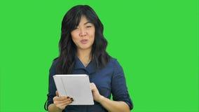 Νέα επιχειρησιακή γυναίκα με τον υπολογιστή ταμπλετών που παρουσιάζει το πρόγραμμα που εξετάζει τη κάμερα για μια πράσινη οθόνη,  απόθεμα βίντεο