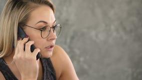 Νέα επιχειρησιακή γυναίκα με το ταραγμένο πρόσωπο, που μιλά στο τηλέφωνο φιλμ μικρού μήκους