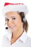 Νέα επιχειρησιακή γυναίκα με το headphose, μικρόφωνο στο καπέλο santa. Στοκ Εικόνες