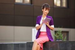 Νέα επιχειρησιακή γυναίκα μόδας στο πορφυρό σακάκι που χρησιμοποιεί τον ψηφιακό υπολογιστή ταμπλετών στοκ εικόνα