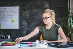 Νέα επιχειρησιακή γυναίκα που εργάζεται στο γραφείο Στοκ Εικόνες