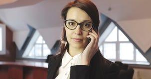 Νέα επιχειρησιακή γυναίκα που μιλά στο κινητό τηλέφωνο στο γραφείο απόθεμα βίντεο