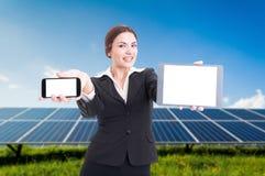 Νέα επιχειρησιακή γυναίκα που παρουσιάζει το σύγχρονες smartphone και την ταμπλέτα Στοκ εικόνες με δικαίωμα ελεύθερης χρήσης