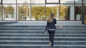 Νέα επιχειρησιακή γυναίκα που περπατά επάνω στα σκαλοπάτια και που κάνει ένα τηλεφώνημα, υπαίθρια απόθεμα βίντεο