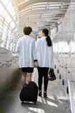 Νέα επιχειρησιακή γυναίκα που τραβά τη βαλίτσα περπατώντας μέσω μιας γέφυρας τροφής επιβατών στοκ φωτογραφία