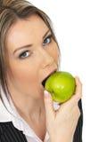 Νέα επιχειρησιακή γυναίκα που τρώει τη φρέσκια ώριμη Juicy πράσινη Apple Στοκ Φωτογραφίες