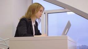 Νέα επιχειρησιακή γυναίκα που χρησιμοποιεί το φορητό προσωπικό υπολογιστή για την εργασία στο επιχειρησιακό γραφείο απόθεμα βίντεο