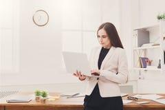Νέα επιχειρησιακή γυναίκα που χρησιμοποιεί το lap-top στο γραφείο Στοκ εικόνα με δικαίωμα ελεύθερης χρήσης