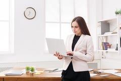 Νέα επιχειρησιακή γυναίκα που χρησιμοποιεί το lap-top στο γραφείο Στοκ φωτογραφία με δικαίωμα ελεύθερης χρήσης