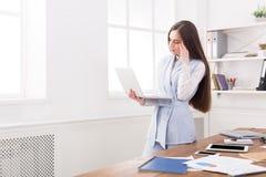 Νέα επιχειρησιακή γυναίκα που χρησιμοποιεί το lap-top στο γραφείο Στοκ Εικόνες