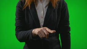 Νέα επιχειρησιακή γυναίκα που ψάχνει τις πληροφορίες για το εικονικό ταμπλό που γλιστρά και που μεγεθύνει με τα δάχτυλα ενάντια σ φιλμ μικρού μήκους