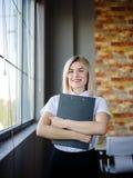 Νέα επιχειρησιακή γυναίκα σε μια άσπρη μπλούζα με έναν φάκελλο κινηματογραφήσεων σε πρώτο πλάνο Στοκ εικόνες με δικαίωμα ελεύθερης χρήσης