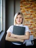 Νέα επιχειρησιακή γυναίκα σε μια άσπρη μπλούζα με έναν φάκελλο κινηματογραφήσεων σε πρώτο πλάνο Στοκ Φωτογραφία