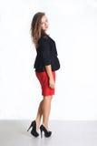 Νέα επιχειρησιακή γυναίκα σε μια κόκκινη φούστα και ένα μαύρο σακάκι Στοκ εικόνα με δικαίωμα ελεύθερης χρήσης