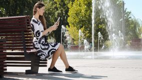 Νέα επιχειρησιακή γυναίκα σε μια συνεδρίαση φορεμάτων σε έναν πάγκο και την ομιλία στην ταμπλέτα απόθεμα βίντεο