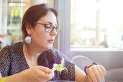 Νέα επιχειρησιακή γυναίκα στο χρόνο μεσημεριανού γεύματος στο εστιατόριο που τρώει τη σαλάτα και που εξετάζει τις έξυπνες μετρώντ Στοκ φωτογραφία με δικαίωμα ελεύθερης χρήσης